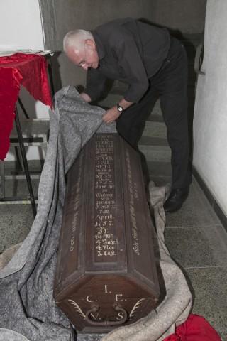 Wolfgang Nethöfel vom Kirchenvorstand der Hoffnungsgemeinde, der die Ausstellung initiiert hat, packt einen Kindersarg aus dem 18. Jahrhundert aus, der ebenfalls zu sehen ist. Foto: Ilona Surrey